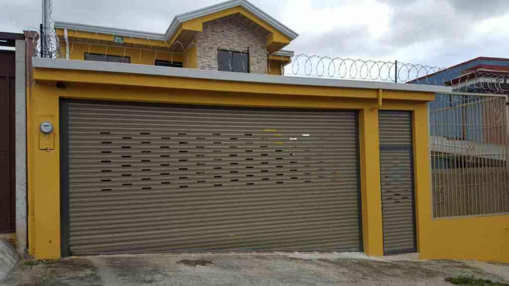 cortina metalica color café en casa color amarillo con una puerta a la par
